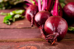 Organic young beets with green leaves on wooden table Royalty Free Stock Images
