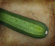 Organic zucchini on an old rustic stone chopping board Stock Photo