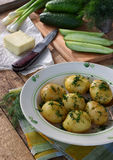 Organically grown new potatoes with butter and dill on wooden background. First spring harvest. Stock Photo