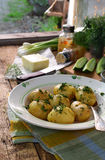 Organically grown new potatoes with butter and dill on wooden background. First spring harvest. Royalty Free Stock Image