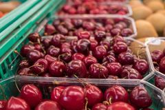 Organics cherry in plastic boxes sold at local city market. Provence. France stock photos