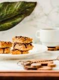 Organicznie Czekoladowy Granola baru tort Plasterki z filiżanka kawy na białym kamiennym tle zdjęcia stock