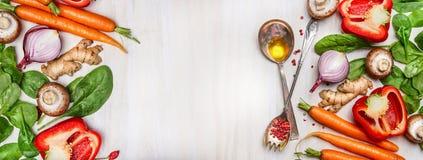 Organicznie czyści warzywa dobierający z kulinarnymi łyżkami i olejem na białym drewnianym tle, odgórny widok, sztandar