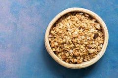 Organicznie domowej roboty granola adra z owsami, dokrętkami i rodzynkami w glinianym pucharze na błękitnym tle, Widok od wierzch zdjęcia stock