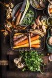 Organicznie korzeniowi warzywa w żniwo koszu na ciemnym nieociosanym kuchennego stołu tle z składnikami dla smakowitego kucharstw fotografia stock