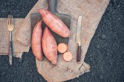 Organicznie korzeniowych warzyw batata lying on the beach na prostackim płótnie i rydlu słuzyć wioskę Jesieni żniwa kopii przestr obraz royalty free