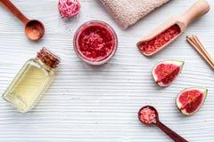 Organicznie kosmetyczny ustawiający z świeżą figą, kąpielową solą, olejem i pętaczką na białego drewnianego tła mieszkania nieatu Obraz Royalty Free