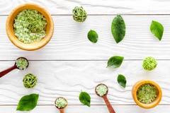 Organicznie kosmetyczny ustawiający z herbacianymi oliwnymi liśćmi i morze solą w pucharu tła białego drewnianego stołowego miesz Fotografia Stock