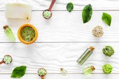 Organicznie kosmetyczny ustawiający z herbacianymi oliwnymi liśćmi i morze solą w pucharu tła białego drewnianego stołowego miesz Obrazy Stock