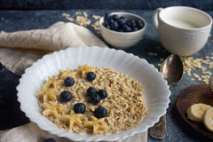 Organicznie oatmeal owsianka z czarną jagodą, banan, miód, mleko na zmroku kamienia stole, zdrowy styl życia i diety pojęcie, Obraz Royalty Free