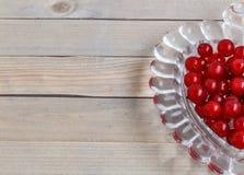 Organicznie ogrodowe jagody na starym drewno stole od above, obecna czerwony krystaliczna waza w formie serca Obrazy Stock