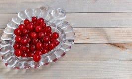 Organicznie ogrodowe jagody na starym drewno stole od above, obecna czerwony krystaliczna waza w formie serca Zdjęcia Stock