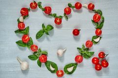 Organicznie składniki dla sałatki na szarym tle: czereśniowi pomidory, świeży basil opuszczają, czosnek alla aubergine tła kuchni zdjęcia stock