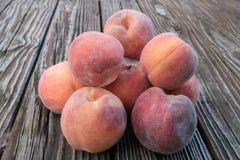 Organicznie, soczyste brzoskwinie na nieociosanym drewnianym stole, obrazy stock
