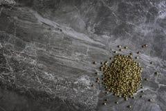 Organicznie wysuszeni kolendrowi ziarna na mable kuchennym worktop tle obraz stock