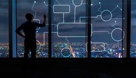 Organigramme avec l'homme par de grandes fenêtres la nuit photographie stock libre de droits