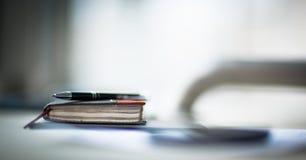 Organisatör och penna på kontorsskrivbordet Arkivfoto