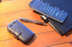 Organisatör, penna och mobiltelefon Arkivfoto