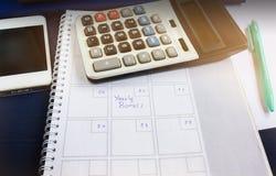 Organisatörbok med den årliga bonusen för text och bakgrund av calculaen Arkivbild