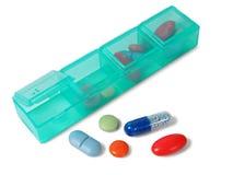 Organisateur de pilules sur le blanc photographie stock