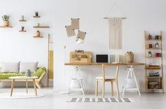 Organisateur intérieur naturel de bureau de siège social, macramé sur un mur, étagères et divan photographie stock