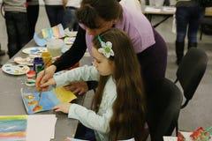 Organisation des Freiwilligen einer zeichnet Farben zusammen mit einem Mädchen Stockfotografie