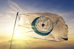 Organisation of Islamic Cooperation OIC flag textile cloth fabric waving on the top sunrise mist fog stock image