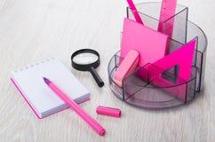 Organisator mit rosa Briefpapierwerkzeugen, Notizblock, Lupe Stockbilder
