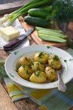 Organisch gewachsene Frühkartoffeln mit Butter und Dill auf hölzernem Hintergrund Erste Frühlingsernte lizenzfreie stockfotografie