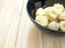 Organische Banane in der schwarzen Schüssel Lizenzfreie Stockfotografie