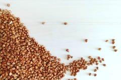 Organische Buchweizengrützen ein weißer hölzerner Hintergrund Bestandteil zum gesundes Frühstück lizenzfreies stockfoto