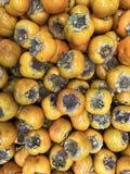 Organische dadelpruimvruchten in stapel bij lokale landbouwersmarkt dadelpruimachtergrond Stock Afbeelding
