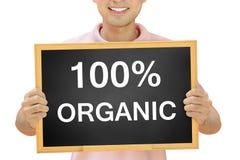 100% ORGANISCHE die tekst op bord door de glimlachende mens wordt gehouden Stock Fotografie