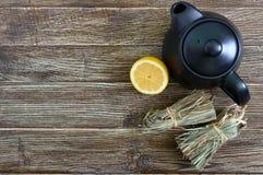 Organische droge flexuosus van citroengrascymbopogon in bossen en citroenfruit op een houten lijst Kruiden voor thee royalty-vrije stock foto's