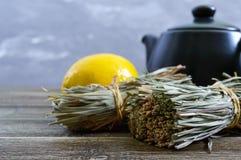 Organische droge flexuosus van citroengrascymbopogon in bossen en citroenfruit op een houten lijst Kruiden voor thee stock foto