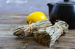 Organische droge flexuosus van citroengrascymbopogon in bossen en citroenfruit op een houten lijst Kruiden voor thee stock foto's