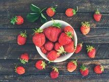 Organische Erdbeeren in der Metallschüssel auf rustikalem hölzernem Hintergrund Sommergeschenk- und -erntekonzept Beschneidungspf stockbild