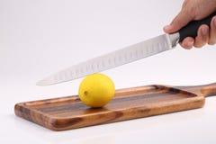 Organische frische Zitrone auf hölzernem Behälter mit Küchenmesser ist in der Hand Lizenzfreie Stockfotografie