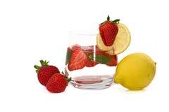 Organische geïsoleerde aardbei, munt en citroen en gegoten water Stock Afbeeldingen