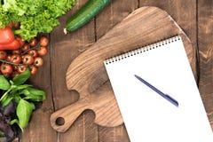 Organische groenten, hakbord en lege blocnote met pen op houten achtergrond Stock Afbeelding
