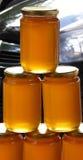 Organische honing in kruiken op een markt Stock Foto's