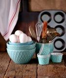 Organische kippeneieren en keukentoebehoren voor het maken cupcakes Rustieke stijl Houten achtergrond Stock Foto's