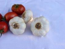 Organische Knoblauchknollen und Tomaten auf der weißen Tischdecke Gesunder Lebensstil des Konzeptes Unscharfer Hintergrund Beschn Stockbild