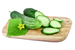 Organische komkommers op een scherpe die raad op wit wordt geïsoleerd Stock Foto's
