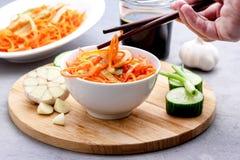 Organische Kruidige Wortelsalade met Komkommer en Knoflook het Concept Houten Tray Female Hand van de Veganistnatuurvoeding Stock Afbeelding