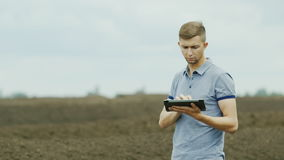 Organische Landwirtschaft Ein junger Landwirt arbeitet nahe Haufen des Komposts, oder Düngemittel, benutzt eine Tablette stock footage