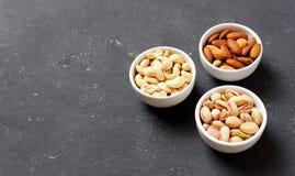 Organische Nüsse, Mandeln, Acajoubaum, Pistazie in Schüsseln, köstlicher Snack Abschluss oben Stockbilder