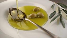 Organische olijfolie Het extra maagdelijke olie inschenken aan de lepel stock video