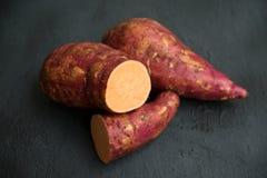 Organische oranje bataat op donkere achtergrond stock foto's