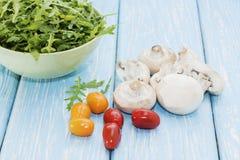 Organische paddestoelen Natuurlijke voeding Verse paddestoelen en arugulasalade, kersentomaten Stock Afbeelding